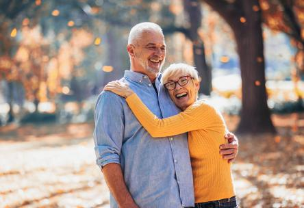 Mature couple hugging on a walk.